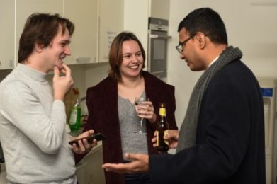 three people laughing and drinking beer