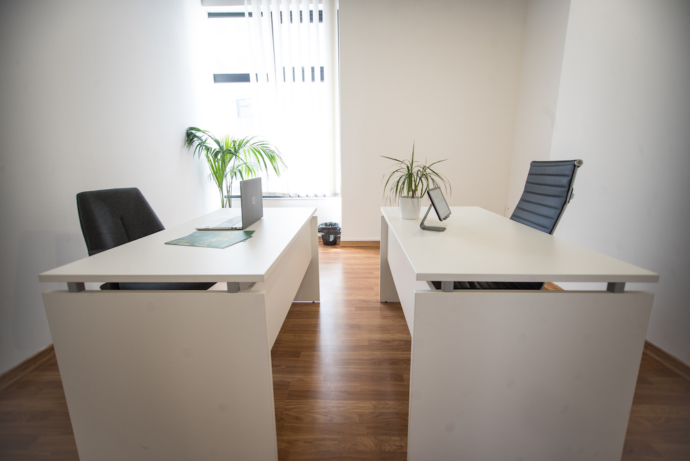 two white desks, and black chairs in a private Office in St Julian's
